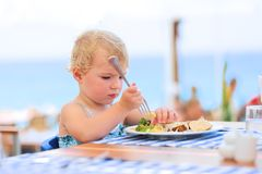 Cute little girl having lunch in resort restaurant Royalty Free Stock Photos