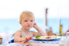 Cute little girl having lunch in resort restaurant Stock Images