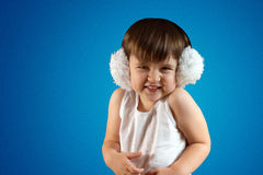 Cute little girl in headphones. On the blue background laughing Stock Photos