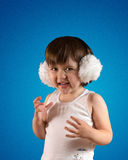 Cute little girl in headphones. On the blue background laughing Stock Image