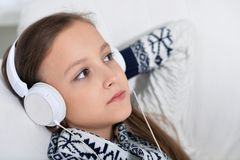 Portrait of little girl in headphones listening to music stock photos