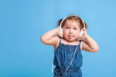 Cute little girl in headphones listening to music using a tablet and smiling on blue background Stock Image