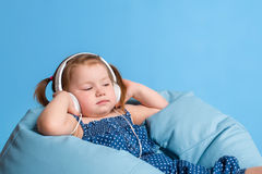 Cute little girl in headphones listening to music using a tablet and smiling while sitting on blue big bag Stock Photography