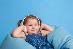 Cute little girl in headphones listening to music using a tablet and smiling while sitting on blue big bag Stock Images