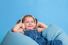 Cute little girl in headphones listening to music using a tablet and smiling while sitting on blue big bag Royalty Free Stock Images