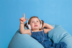 Cute little girl in headphones listening to music using a tablet and smiling while sitting on blue big bag Royalty Free Stock Photography