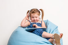Cute little girl in headphones listening to music using a tablet and smiling while sitting on blue big bag Royalty Free Stock Image