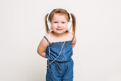 Cute little girl in headphones listening to music using a tablet and smiling on white background Stock Photos