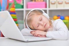 Cute little girl sleeping near laptop Royalty Free Stock Photography