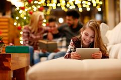 little girl with headphones is using a tablet and smiling on Christmas day. stock image