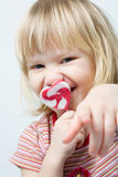 Cute little girl with a heart shape lollipop. Cute little girl eating a heart shape lollipop Stock Image