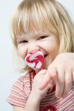 Cute little girl with a heart shape lollipop Stock Image