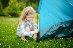Cute little girl helping her parents to set up a tent on a campsite. Active lifestyle, family recreational weekend, summer outdoor stock image