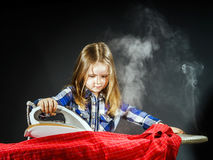 Cute little girl helping your mother by ironing clothes, contras Royalty Free Stock Photo