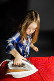 Cute little girl helping your mother by ironing clothes, contras Stock Photos
