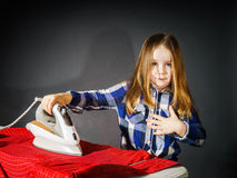Cute little girl helping your mother by ironing clothes, contras Stock Photography