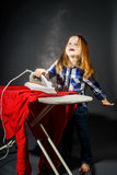 Cute little girl helping your mother by ironing clothes, contras Stock Image
