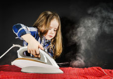 Cute little girl helping your mother by ironing clothes, contras Royalty Free Stock Photography