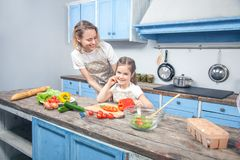 Cute little girl and her beautiful mom in chef`s hats are cutting vegetables and smiling while cooking in kitchen at home royalty free stock images