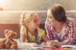 Cute Little Girl and Her Beautiful Mother Drawing. royalty free stock photography