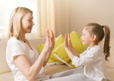 Cute little girl and her beautiful mother are playing games at home, clapping hands together stock photo