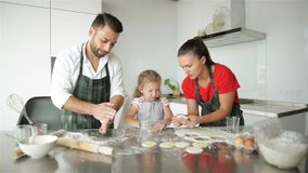 Cute little girl and her beautiful parents are cooking. They have a lot of fun together and smiling in kitchen at home. stock footage