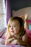 A cute little girl on her bed with a cheeky smile. A cute little girl is in her bedroom on her bed near the window. She is looking at the camera with a cheeky royalty free stock photography
