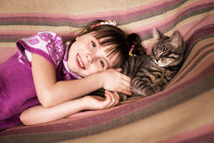 Cute little girl with her beloved cat. Lying on the sofa Stock Photos