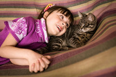 Cute little girl with her beloved cat. Lying on the sofa Stock Images