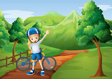 A cute little girl and her bike at the pathway near the wooden f Royalty Free Stock Images