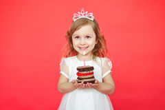 Cute little girl and her birthday cake on red background Stock Image