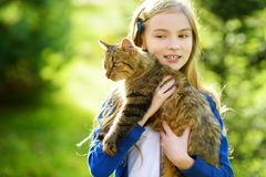 Cute little girl with her cat on sunny autumn day. Adorable child holding het pet kitty. stock photography