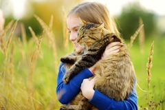 Cute little girl with her cat on sunny autumn day. Adorable child holding het pet kitty. stock photos