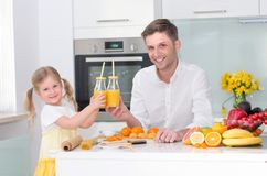 Cute little girl and her dad drinking juice. royalty free stock photo