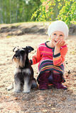 Little girl and her dog sitting on the sand Stock Image