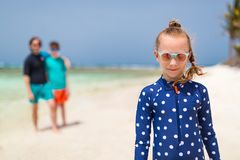 Family at Caribbean beach. Cute little girl and her family enjoying beach vacation on tropical island in Caribbean stock photo