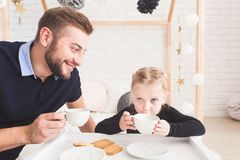 Cute little girl and her father drink tea with cookies at home. stock photos