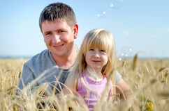 Cute little girl with her father in a wheat field Stock Photo