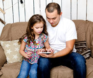 Cute little girl and her fayher with tablet pc Stock Images