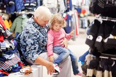 Cute little girl and her grandmother choosing clothes in the shop. Adorable toddler girl and her grandmother in children apparel store, buying clothes, home Stock Photography