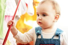 Cute little girl with her hand on a red stick Royalty Free Stock Photos