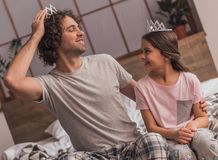 Dad and daughter. Cute little girl and her handsome dad in crowns are talking and smiling while playing together at home stock photos