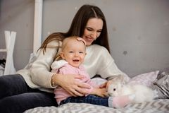 Cute little girl and her mom playing with white rabbit royalty free stock images
