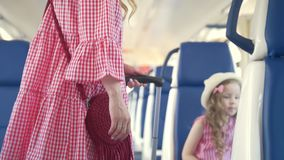 Cute little girl with her mom walks into the train car to their seats. Close up stock video