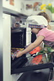 Cute little girl with her mother baking cookies in oven Royalty Free Stock Image