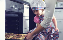 Cute little girl with her mother baking cookies in oven Stock Images