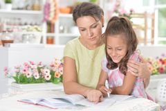 Cute little girl with her mother doing homework together royalty free stock photos