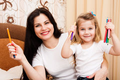 Cute little girl with her mother for drawing. Stock Photos