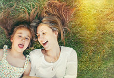 Cute little girl and her mother having fun on the grass in sunny Royalty Free Stock Photos