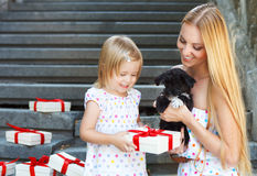 Cute little girl and her mother hugging dog puppies Royalty Free Stock Photo